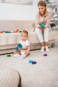 Fotografie roztomilé batole při pohledu na fotoaparát a hrát si s barevnými kostkami a matka