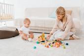 Fotografie roztomilé batole hraje s barevnými kostkami a matkou v dětskej pokoj