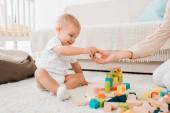 Fotografie roztomilé batole hraje s barevné kostky v dětskej pokoj