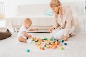 roztomilé batole hraje s barevnými kostkami a matkou v dětskej pokoj