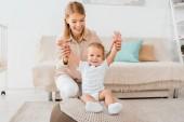 roztomilé batole pozvedá ruce s matkou v dětskej pokoj