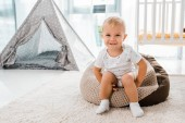 Photo adorable smiling toddler sitting on bean bag chair and looking at camera in nursery room