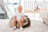 Photo adorable smiling toddler sitting on bean bag chair  in nursery room