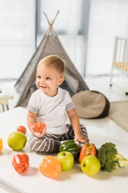 cute smiling toddler sitting on table surrounded by fruit and vegetables