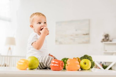 cute toddler eating and sitting on table surrounded by fruit and vegetables
