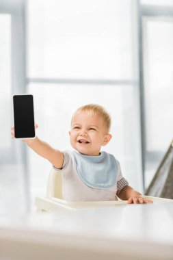 cute smiling toddler holding smartphone in hand and sitting in baby chair