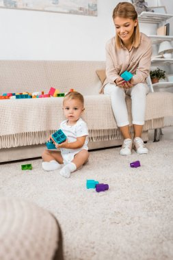 adorable toddler looking at camera and playing with colorful cubes and mother