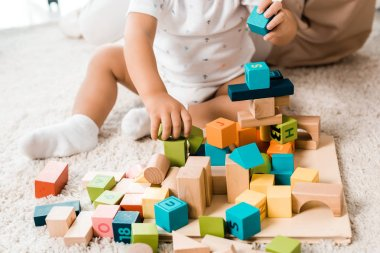 Cropped view of adorable toddler playing with colorful cubes stock vector