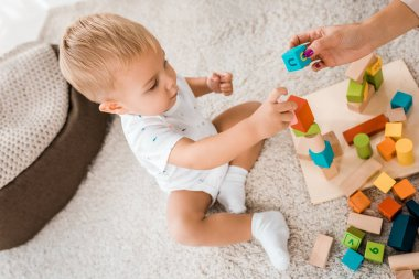 angle view on adorable toddler playing with colorful cubes in nursery room