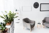 Modernes Interieur der Wartehalle mit grauen Sesseln und Pflanzen
