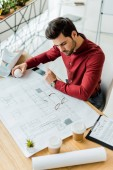 handsome male architect sitting and working on blueprint in office