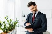 hezký usmívající se podnikatel v oblasti formálního oblečení, psaní v poznámkovém bloku v úřadu