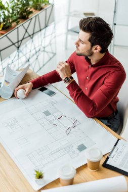 Handsome male architect sitting and working on blueprint in office stock vector