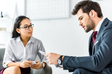 asian businesswoman looking at businessman with newspaper in office