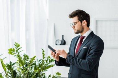 handsome businessman in formal wear using smartphone in office