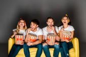 Fotografie cheerful young friends sitting on yellow couch, watching movie and eating popcorn from boxes on grey