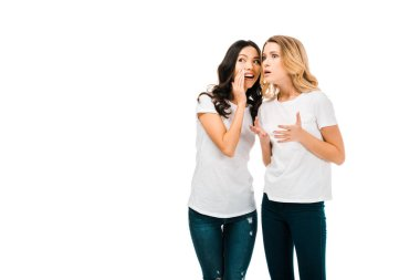 smiling young woman whispering something to shocked girlfriend isolated on white