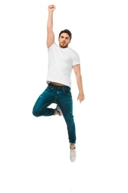 serious handsome man jumping with raised hand and looking at camera isolated on white