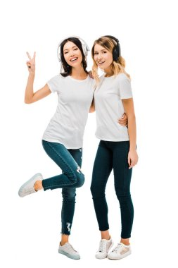beautiful happy girls in headphones standing together and showing victory sign isolated on white