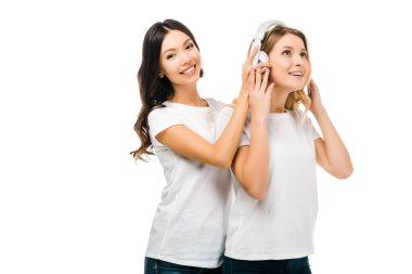 beautiful happy girls in white t-shirts using headphones together isolated on white