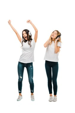 full length view of happy girls listening music in headphones and dancing isolated on white
