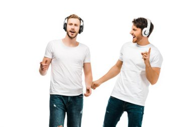 smiling young men listening music in headphones and singing isolated on white