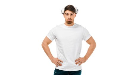 serious man with headphones on head standing with hands on waist and looking at camera isolated on white