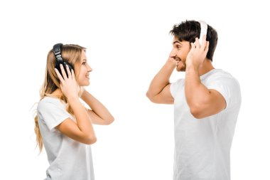 side view of young couple listening music in headphones and smiling each other isolated on white