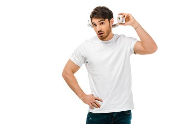 young man with open mouth holding headphones and looking at camera isolated on white