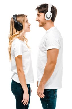 side view of happy young couple in headphones standing together and smiling each other isolated on white