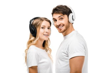 happy young couple in white t-shirts and headphones smiling at camera isolated on white