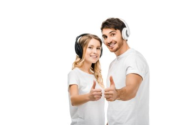 happy young couple in headphones showing thumbs up and smiling at camera isolated on white