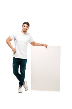 Full length view of handsome young man standing with blank placard and smiling at camera isolated on white stock vector