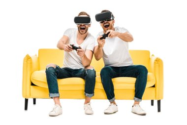 excited young men in virtual reality headsets playing with joysticks isolated on white