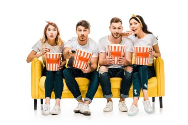 young friends holding popcorn boxes and watching tv while sitting on yellow sofa isolated on white