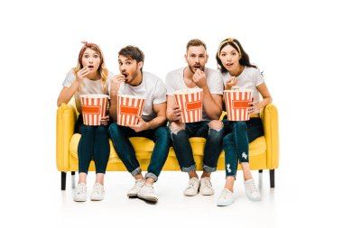 young friends eating popcorn from boxes and looking at camera while sitting on yellow sofa isolated on white
