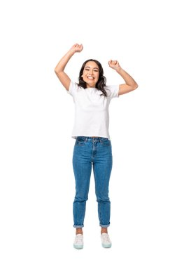 Happy asian smiling girl in white t-shirt and blue jeans standing with hands up isolated on white