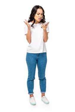 Angry asian girl in white t-shirt and blue jeans using smartphone isolated on white