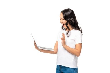 Smiling young asian woman using laptop and showing hello gesture isolated on white