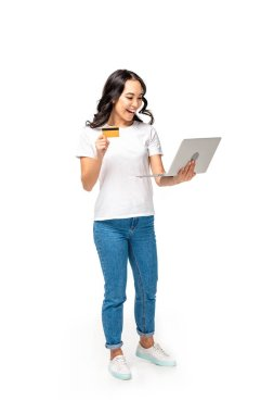 Happy asian woman in white t-shirt and blue jeans using laptop and holding credit card isolated on white