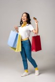 Photo trendy dressed asian woman holding colorful shopping bags and showing credit card on grey