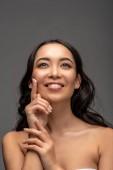 usmívající se krásná Asijská dívka použitím kosmetický krém na obličej izolované Grey