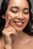 Portrét s úsměvem Krásná Asiatka se zavřenýma očima použitím kosmetický krém na obličej izolované Grey