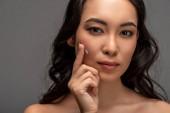Fényképek Kozmetikai krém alkalmazása arcon és látszó-on fényképezőgép, szürke elszigetelt, gyönyörű ázsiai lány portréja