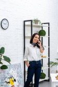 Fotografie Smiling asian freelancer talking on smartphone and holding hand in pocket while standing by shelves unit at home