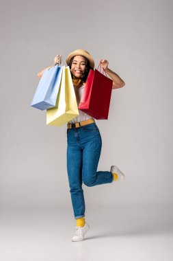 Happy trendy dressed asian woman holding colorful shopping bags on raised hand on grey