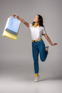 Happy asian woman holding colorful shopping bags in stretched hand on grey