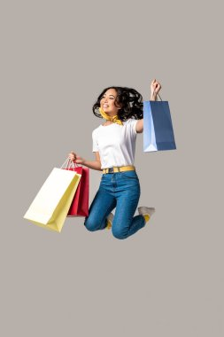 Excited asian woman holding colorful shopping bags and happily jumping with one raised hand isolated on grey