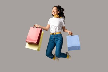 Laughing asian woman holding colorful shopping bags and happily jumping isolated on grey