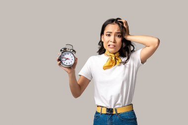 Shocked young asian woman showing alarm clock and holding hand on head isolated in grey